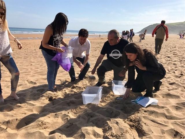 Estudiantes participan en la recogida de microplásticos en la playa de Zarautz